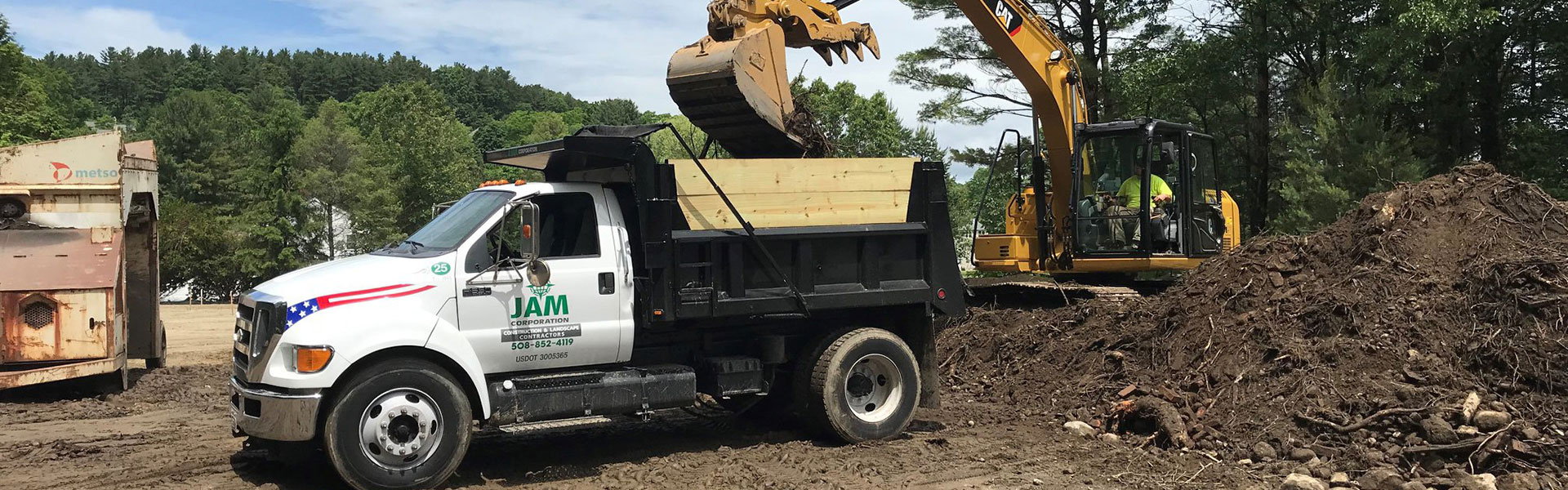JAM Corporation excavator tractor dumping dirt into the back of a truck on a work site