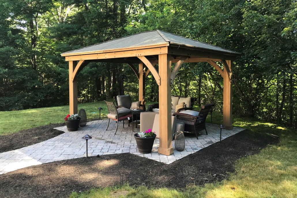 Newlay crafted and landscaped gazebo on stone patio with stone walkway in backyard of house